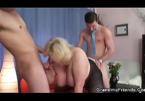 Three men horseplay with well-endowed blonde granny